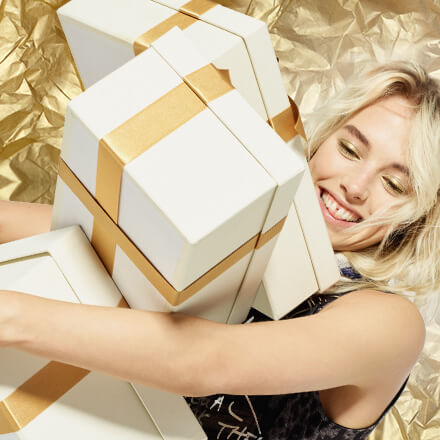 Desigual digital creative of a woman holding three gift boxes